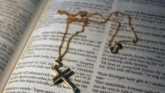 Goldene Kette mit Kreuz-Anhänger auf einer Bibel in schwedischer Sprache.