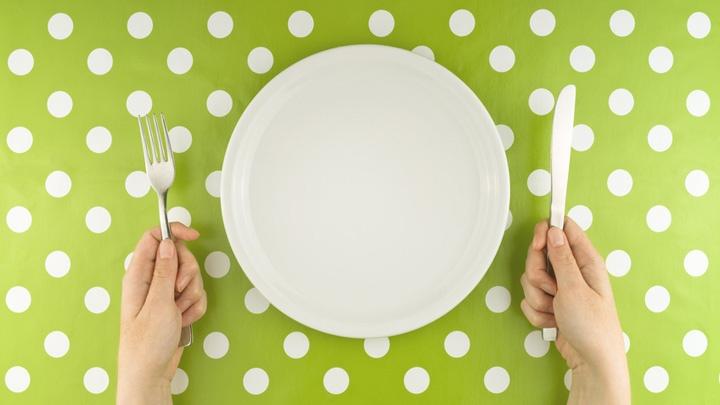 Hände mit Messer und Gabel neben einem leeren Teller.