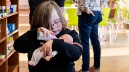 Nora, ein Kind mit Down-Syndrom, spielt im Eltern-Kind-Treff mit einer Puppe.
