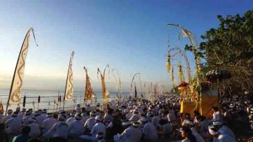 Menschen in festlichen Gewändern vor goldenen Altären und Tempelfahnen am Strand von Bali