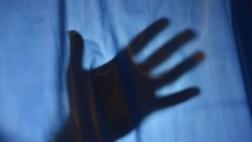 Der Schatten einer Hand zeichnet sich hinter einem Vorhang ab.