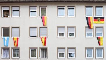 Nationalflaggen verschiedener Länder hängen an Fenstern eines Mehrfamilienhauses.