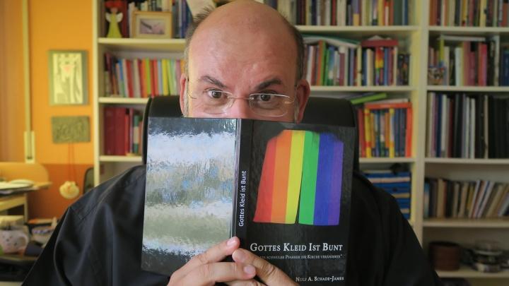"""Nulf Schade-James mit seiner Autobiografie """"Gottes Kleid ist bunt""""."""