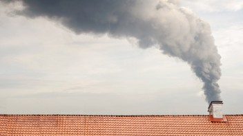Dichter Rauch steigt aus dem Schornstein eines Gebäudes.