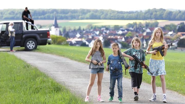 Die Fotos zeigen Kinder mit Maschinengewehren vor idyllischer Landschaft.