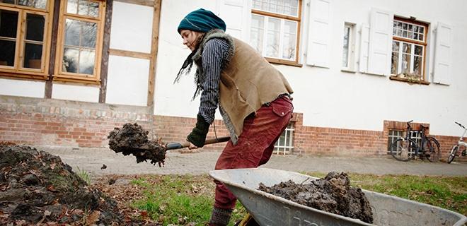 Die reisende Lehmbauerin Daria Anatzki schaufelt Naturlehm in eine Schubkarre.