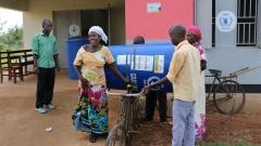 Eine Bäuerin holt am 18.01.2016 in einem Büro des Welternährungsprogramms (WFP) im Iganga Distrikt in Uganda eine Plastiktonne ab in der sie ihre Ernte lagern kann.