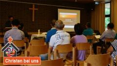 Mitglieder der chinesischen Gemeinde in München sitzen im Gottesdienst.