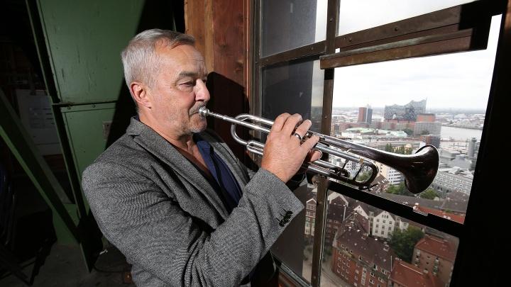 Michel-Türmer Horst Huhn spielt im 7. Stock des Turmes der Hauptkirche St. Michaelis in Hamburg aus einem Fenster Trompete.