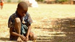 Ein Kind hat  in Khulubvi im Süden von Malawi bei einer Lebensmittelverteilung Maiskörner aufgesammelt (Archiv).
