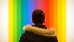 Rückansicht eines Mannes vor einer Wand in Regenbogenfarben.