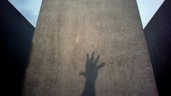 Schatten einer in die Höhe gestreckten Hand auf einer Stele des Holocaust-Mahnmals in Berlin.