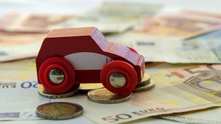 Ein rotes Spielzeugauto aus Holz steht auf Geldscheinen und Münzen.
