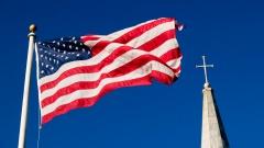 US-Flagge und Kirchturm mit Kreuz vor blauem Himmel.