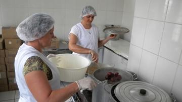 Frauen kochen in der Großküche der Landkooperative Obst und Gemüse ein.