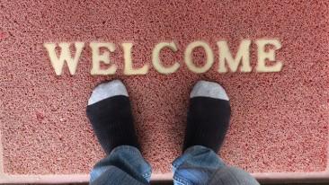 """Ein Mann steht in Strümpfen auf einer Fußmatte, auf der das Wort """"Welcome"""" steht."""