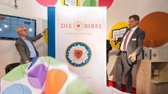 Heinrich Riethmüller, Vorsteher des Börsenvereins des Deutschen Buchhandels (l.), und Christoph Rösel, Generalsekretär der Deutschen Bibelgesellschaft, enthüllen die neue Lutherbibel mit der Lutherrose auf dem Buchcover.