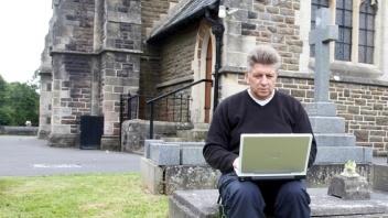 Pfarrer mit Laptop vor der Kirche