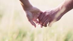 Die Hände eines Paares greifen ineinander.