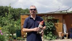 Necati Cavdar steht mit einem Gartenzwerg in der Hand in seiner Parzelle im Frankfurter Kleingartenverein.