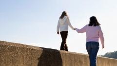Ein Mädchen balanciert an der Hand ihrer Mutter auf einer Mauer.