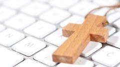 Kette mit einem Kreuzanhänger aus Holz liegt auf einer Computertastatur.