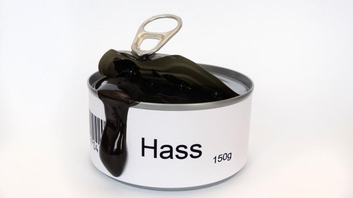 """Aus einer Konservendose mit der Aufschrift """"Hass"""" läuft eine schwarze Flüssigkeit."""