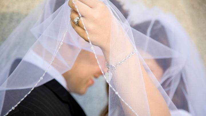 Brautpaar unter einem Schleier.