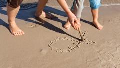 Vater und Kind malen am Strand das Ichthys-Symbol in den Sand.
