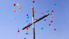 Bunte Luftballons fliegen über einem Holzkreuz in den Himmel.