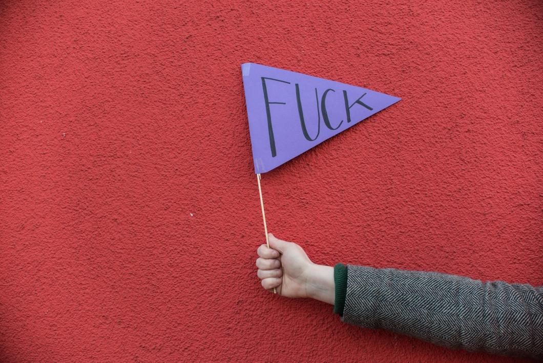 """Hand mit Fahne auf der """"Fuck"""" steht."""