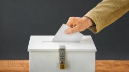 Eine Hand steckt einen Wahlumschlag in eine Box.