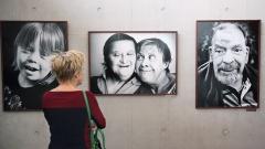 """Besucherin blickt in der Ausstellung """"Wir sind viele"""" auf Porträts von Menschen aus Bethel."""