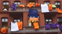 Rund 50 bunte Bettdecken und Kissen wurden an den Fenstern eines Landeskirchengebäudes in Berlin gelüftet, um für private Gastgeber zum Kirchentag zu werben.