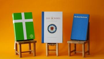 Drei Bibeln auf kleinen Stühlchen, in der Mitte die Lutherbibel 2017.