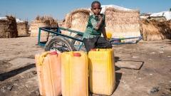 In Maiduguri in Nigeria sammeln Menschen an einem öffentlichen Bohrloch ihr Wasser. Sie sind vor der Gewalt Boko Harams aus ihren Dörfern geflohen. Ein Junge steht hinter Wasserkanistern.