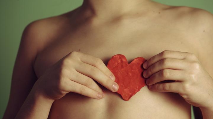 Junge hält ein Herz aus Papier vor seinen Oberkörper.