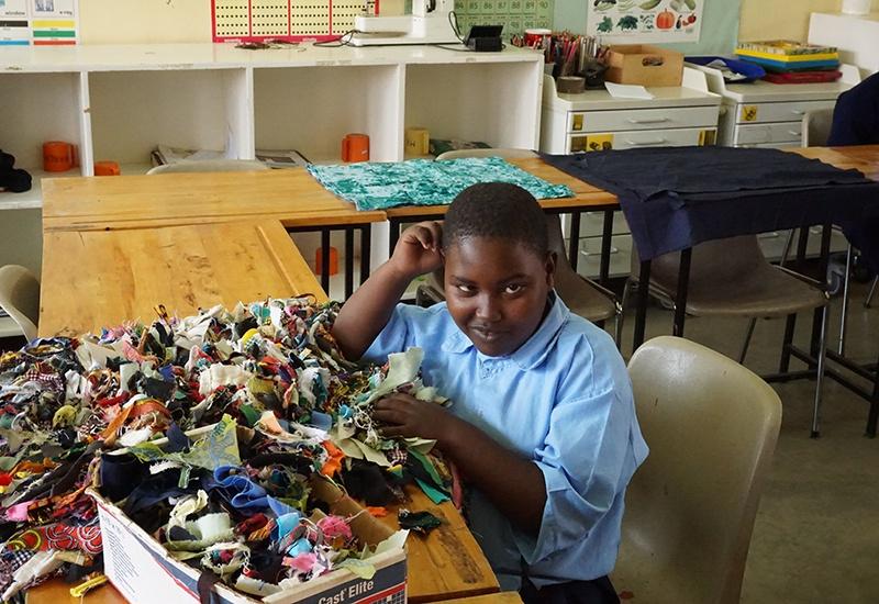 Ein Mädchen mit Behinderung sitzt an einem Tisch und sortiert bunte Stofffetzen. Sie ist Schülerin in einer Spezialklasse.