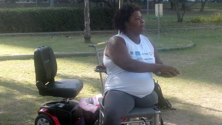 Rosinha dos Santos sitzt auf einem Gestell in einem Park und trainiert, im Hintergrund steht ihr Rollstuhl.