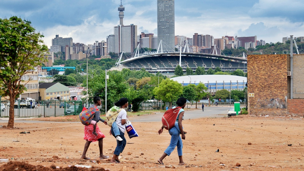 Drei junge Mütter tragen ihre Kinder auf dem Rücken. Im Hintergrund ist die Skyline von Johannesburg zu sehen.