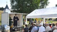Im sonnigen Dreis in der Eifel versammeln sich Menschen am 12.07.15 zum Gottesdienst mit Pfarrer Frank Meckelburg an einer Kirche auf Raedern.