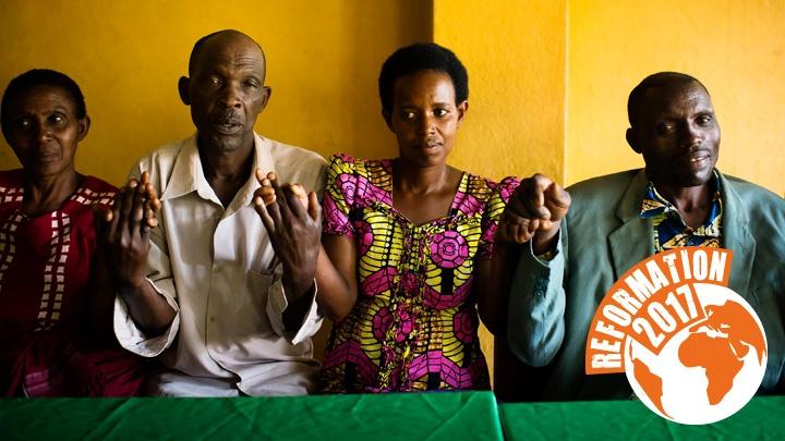 Männer und Frauen aus der Gemeinde in Remera, Ruanda, halten sich an den Händen.