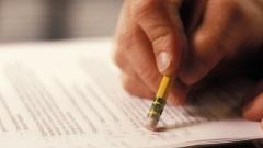 Eine Person radiert Kommentare auf einem Manuskript aus.