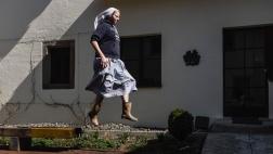 Schwester Clara springt im Garten des Kapuzinerkloster Stühlingen nach getaner Arbeit von einer Bank.