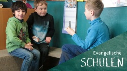 Drei Schüler spielen ein Rechenspiel mit Karten.