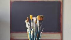 Mehrere Pinsel stehen vor einem abstrakten Gemälde.