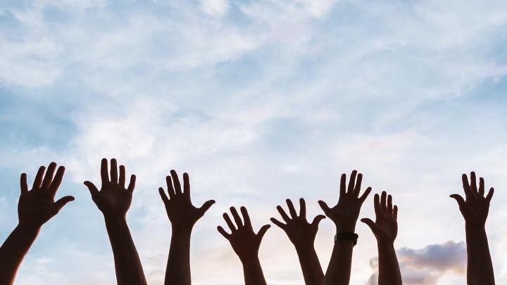 Hände strecken sich in den Himmel.