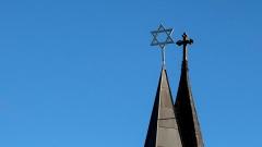 Turmdach mit Kreuz neben Turmdach mit Davidsstern vor blauem Himmel