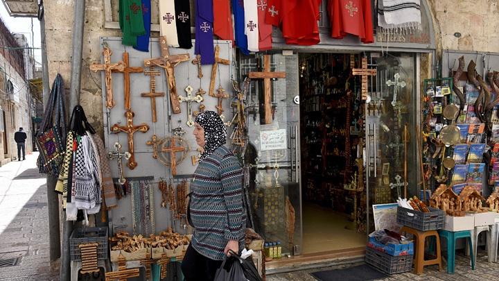 Ein Palästinenserin geht auf der Via Dolorosa, dem Leidensweg Christi zur Kreuzigung, an einem Souvenirladen vorbei. In den Kassen der palästinensischen Souvenirhaendler hinterlässt die Gewalt in der Region tiefe Spuren.