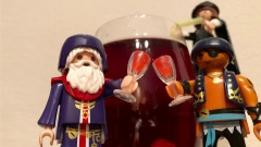Zwei Playmobilpuppen prosten sich mit Weingläsern zu: Interpretation des Talmudabschnitts zu Purim, in dem steht, man soll trinken bis zwischen verflucht sei Haman und gesegnet sei Mordechai nicht mehr zu unterscheiden ist.